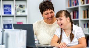 Support worker laughing with young disabled girl, both looking at a laptop